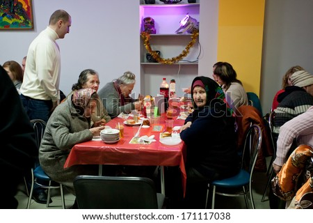 KIEV, UKRAINE - DEC 10: Elderly poor women have a food at the Christmas charity dinner for the homeless on December 10, 2013, in Kyiv, Ukraine. About 100,000 adults are homeless in Ukraine. - stock photo