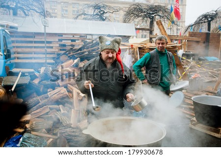 KIEV, UKRAINE - DEC 12: Men cook traditional soup in huge pans outdoor during anti-government Euromaidan protest on December 12 2013. More than 800,000 protesters participated in Kiev's Euromaidan - stock photo