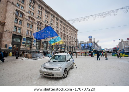 KIEV, UKRAINE - DEC 10: One car with national and EU flags on the empty snow street in the occupied territory by demonstrators during anti-government protest Euromaidan on December 10, 2013 in Kyiv - stock photo