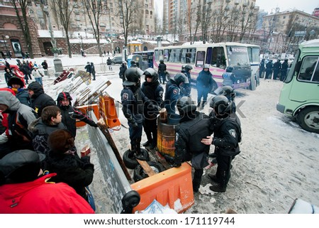 KIEV, UKRAINE - DEC 10: Paramilitary group of policemen in uniform standing at the barricades, protesters protected, during anti-government protest Euromaidan on December 10, 2013 in Kyiv, Ukraine. - stock photo