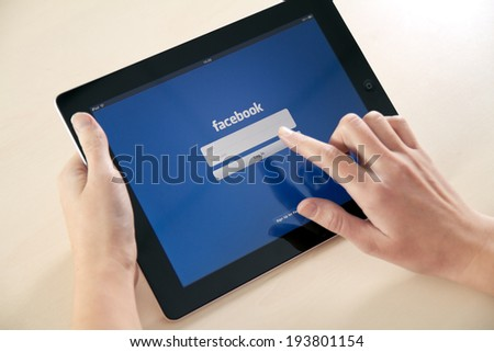 KIEV, UKRAINE - DECEMBER 03, 2011: A girl trying to log in Facebook application using Apple iPad. Facebook is largest and most popular social networking site in the world. - stock photo