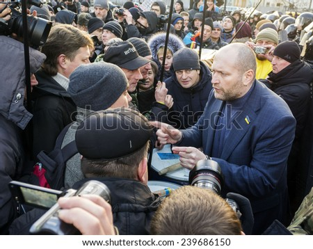 KIEV, UKRAINE - December 23, 2014: Deputy Borislav Bereza tries to calm protesters -- To break through the cordon of police and four special forces in full uniform - stock photo