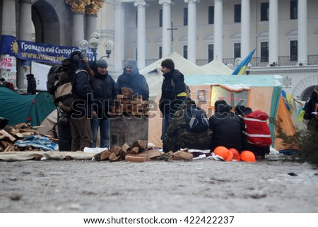 Kiev, Ukraine - December 11, 2013: Mass anti-government protest EuroMaydan in the center of Kiev (Maidan Nezalezhnosti). Protesters are heated by the fire