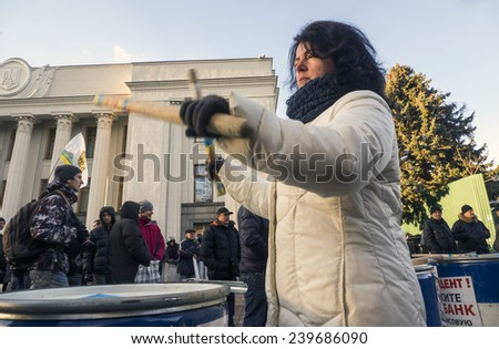 KIEV, UKRAINE - December 23, 2014: Woman protesting drumming on metal barrel on the background of the Verkhovna Rada. -- To break through the cordon of police and four special forces in full uniform - stock photo