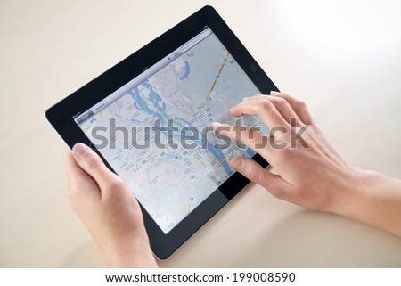 KIEV, UKRAINE - DECEMBER 03, 2011: Woman using Google Maps application on a brand new black Apple iPad. Apple iPad2 is designed and development by Apple inc. and launched in march 2011. - stock photo