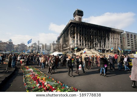KIEV, UKRAINE - FEB 24: Lot of different people with flowers walking past burnt building to honor the memory of 100 people were killed on the street during civil rally on Fabruary 24, 2014, in Kyiv.   - stock photo
