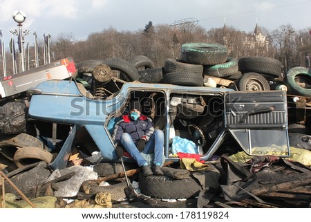 KIEV, UKRAINE - FEB 21, 2014: Protester seats inside the car, which is a part of barricade.