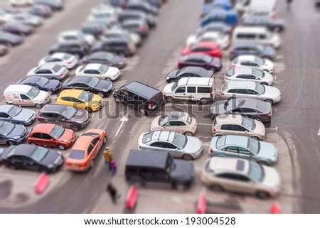 KIEV, UKRAINE - February 15, 2014: Cars parked at a park and side lot at a new entertainment center Blockbuster in Kiev. Tilt-shift effect - stock photo