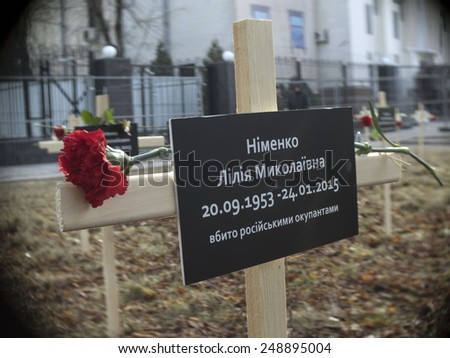 "KIEV, UKRAINE - February 1, 2015: Cross with a sign that says ""Lily Nimenko, killed by Russian occupiers"" near the Russian Embassy in Kiev, Ukraine, Sunday, Feb. 1, 2015. - stock photo"