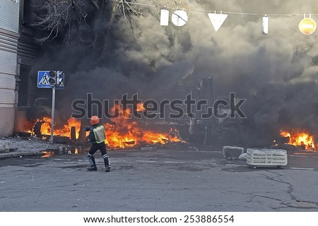 KIEV UKRAINE-FEBRUARY 18, 2014: Fire protecting by defend oneself protesters of armed special forces attack at first day of mass shooting at Euromaydan time. Protester in plastic helmet tosses a stone