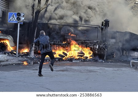 KIEV UKRAINE -FEBRUARY 18, 2014: Fire protecting by defend oneself protesters of  armed special forces attack at first day of mass shooting at Euromaydan time. Unknown young protester tosses a stone