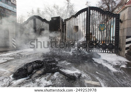 "KIEV, UKRAINE - FEBRUARY, 2, 2015: Firefighter extinguishes burning tires near the Ministry of Defense of Ukraine during rally soldiers of the volunteer battalion ""Aydar"" - stock photo"