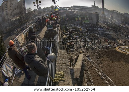 Kiev, Ukraine - February 20, 2014: Freed from government troops Evromaydan. The smoke protesters hiding from snipers, collecting stones and bottles at the devastated area to the forward position,
