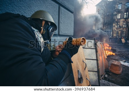 Kiev, Ukraine - 18 February 2014: Protester ignites a smoke bomb to stop the riot police, because police wants to oust protesters from the government quarter. Violent confrontation on Instytutska Str - stock photo