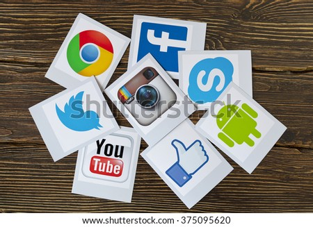 Kiev, Ukraine - February 09, 2015: Set of most popular social media icons: Twitter,Youtube, Instagram, Facebook, Skype, Google Chrome, Android,  printed on paper and scattered on the wooden table - stock photo