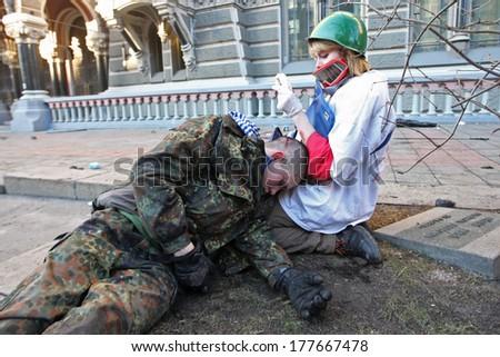 KIEV, UKRAINE - FEBRUARY 18, 2014: The doctor provides medical care to an unconscious person. Kiev, Ukraine, Kiev, 18.02.2014 - stock photo