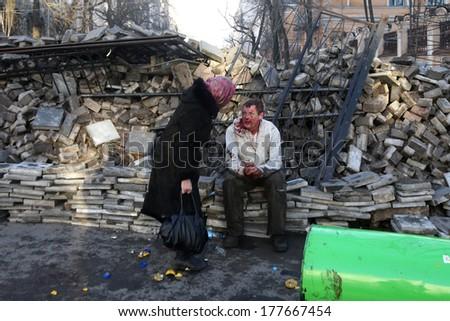 KIEV, UKRAINE - FEBRUARY 18, 2014: Woman assisting the victim. Kiev, Ukraine, Kiev, 18.02.2014 - stock photo