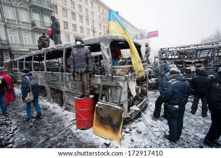 KIEV, UKRAINE - JAN 21: Civil guardians wait for attack of policemen on the barricades of occupying snow street during winter anti-government protest Euromaidan on January 21, 2014, in Kyiv, Ukraine  - stock photo