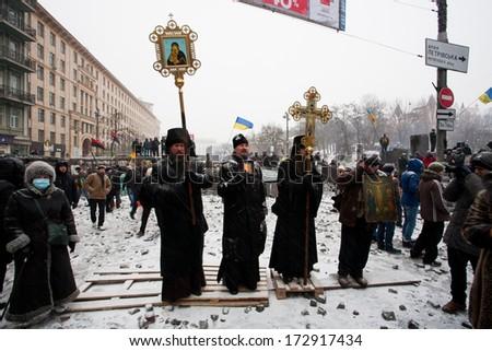 KIEV, UKRAINE - JAN 21: Crowd of people listen praying clergy of Ukrainian Orthodox Church on the snow winter street during anti-government protest Euromaidan on January 21, 2014, in Kyiv, Ukraine.  - stock photo