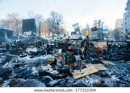KIEV, UKRAINE - JAN 29: Group of guards of revolutionary barricades standing near the special forces on snow ruined street during winter anti-government protest Euromaidan on January 29, 2014, in Kyiv - stock photo