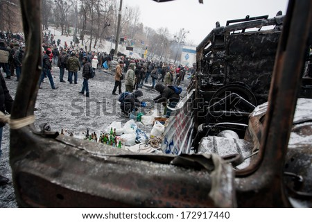 KIEV, UKRAINE - JAN 21: Many active people walk around the winter snowy street with burned cars and buses during anti-government protest Euromaidan on January 21, 2014, in center of Kyiv, Ukraine  - stock photo