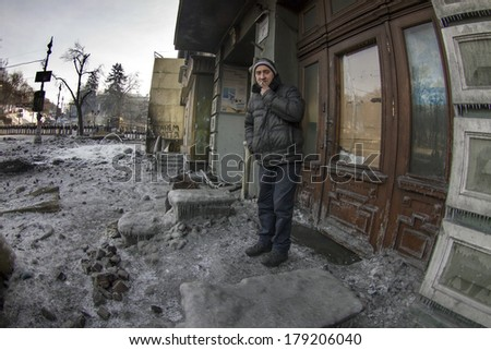 KIEV, UKRAINE - JAN 27, 2014: Temporary truce after-death battles and demonstrators lull, the man lives in the house, through which the front line, and left the house to smoke