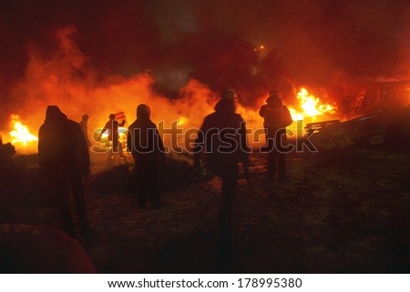Kiev, Ukraine - January 22, 2014: Among the flame burning wheels rebel fighters try to contain the offensive by government forces on the street Hrushevskoho burn buses and trucks police