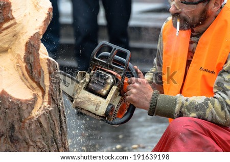 KIEV, UKRAINE, 2 JANUARY 2014: artist carving wood with chainsaw during euromaidan in ukraine