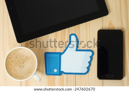 KIEV, UKRAINE - JANUARY 24, 2015: Facebook thumbs up sign printed on paper and placed on wooden background with coffee, iPad and smart phone. Facebook is a well-known social networking service. - stock photo