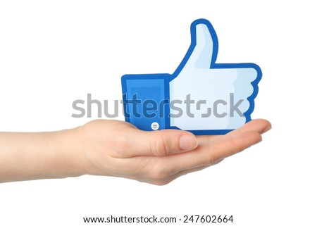 KIEV, UKRAINE - JANUARY 24, 2015: Hand holds facebook thumbs up sign printed on paper on white background. Facebook is a well-known social networking service. - stock photo