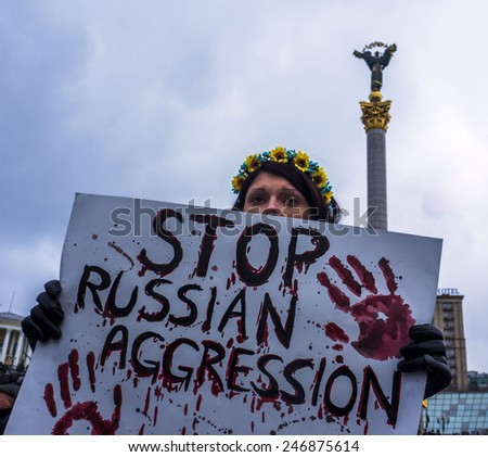 KIEV, UKRAINE - January 22, 2015: Indifferent Ukrainian holds a placard against Russian aggression.  - stock photo