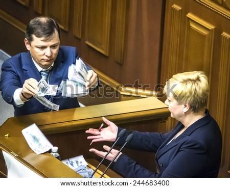 KIEV, UKRAINE - January 16, 2015: Oleg Lyaschko, leader of the 'Radical Party' throws monetary notes on the pulpit during a speech from Valeria Hontareva, chairperson of the Ukrainian national bank - stock photo
