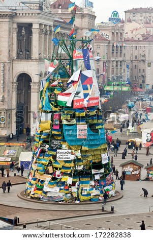 Kiev, Ukraine, January 20, 2014: People near the carcass of the Christmas tree with national flags and placards during a meetings on Maydan in Kiev. - stock photo