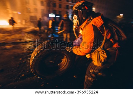 Kiev, Ukraine - 22 January, 2014: Protesters burn tires to stop the riot police, because Ukrainian police want to storm the main anti-government protest camp in the Kiev. Revolution in Ukraine - stock photo