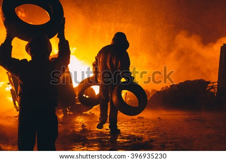 Kiev, Ukraine - 22 January, 2014: Protesters burn tires to stop the riot police, because Ukrainian police want to storm the main anti-government protest camp in the Kiev. Revolution in Ukraine. - stock photo