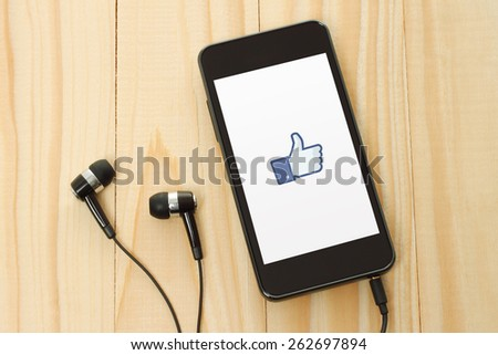 KIEV, UKRAINE - JANUARY 10, 2015: Smart phone with Facebook thumbs up sign on its screen and headphones on wooden background. - stock photo
