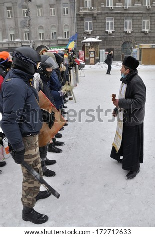 KIEV, UKRAINE � 22 JANUARY 2014: Unknown demonstrators speak with priest before fights with police in government district on January 22, 2014 in Kiev, Ukraine.