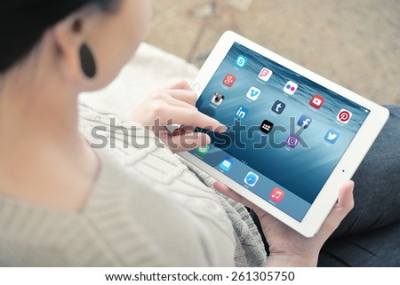 KIEV, UKRAINE - JANUARY 29, 2015: Woman using social media apps on a brand new white Apple iPad Air 2, 6th generation of the iPad, developed by Apple inc. and was released on October 16, 2014 - stock photo