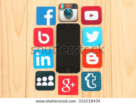 KIEV, UKRAINE - JULY 01, 2015: Famous social media icons such as: Facebook, Twitter, Blogger, Linkedin, Tumblr, Myspace and others, printed on paper and placed around iPhone on wooden background - stock photo
