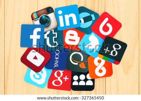 Kiev, Ukraine - July 01, 2015: Famous social media icons such as: Facebook, Twitter, Blogger, Linkedin, Tumblr, Myspace and others, printed on paper and placed around on wooden background. - stock photo