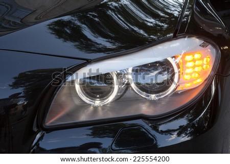 KIEV, UKRAINE - JULY 27, 2012: Headlights of a 7 series BMW car - stock photo