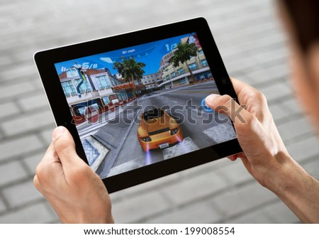 KIEV, UKRAINE - JULY 31, 2011:  Man playing Asphalt 6 game on brand new Apple iPad. Apple iPad2 develop by Apple inc. and launched in March, 2011. Asphalt 6 is a game application, develop by Gameloft. - stock photo