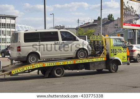 KIEV, UKRAINE - JUNE 3, 2016: A tow truck picking up a car being badly parked in Kiev, Ukraine - stock photo