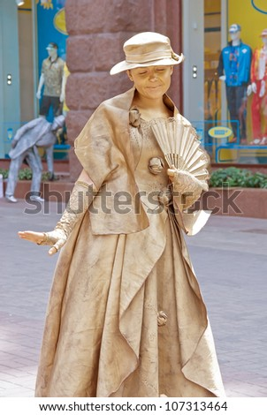 KIEV, UKRAINE - JUNE 30: An unidentified busking mime performs on Khreshchatyk street in Kiev, Ukraine on June 30, 2012. Living bronze statue is the entertainment for the tourists. - stock photo