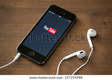KIEV, UKRAINE - JUNE 05, 2014: Brand new Apple iPhone 5S with YouTube app on the screen lying on desk with headphones. YouTube is the popular online video-sharing website, founded in February 14, 2005 - stock photo