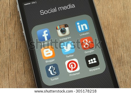 KIEV, UKRAINE - JUNE 23, 2015: iPhone with popular social media icons on its screen on wooden background - stock photo