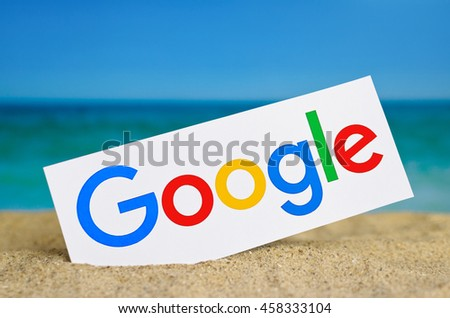 Kiev, Ukraine - June 22, 2016: Logo largest Internet search engine Google printed on paper and placed in the sand against the sea. Google it is the largest Internet search engine, owned of Google.