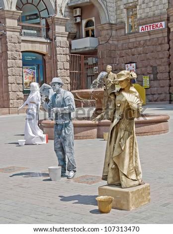 KIEV, UKRAINE - JUNE 30: Unidentified busking mimes perform on Khreshchatyk street in Kiev, Ukraine on June 30, 2012. Living statues are the entertainment for the tourists. - stock photo