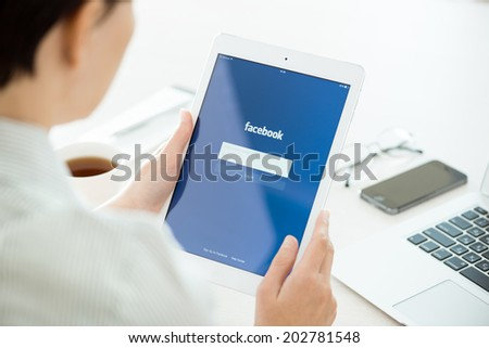 KIEV, UKRAINE - JUNE 27, 2014: Woman looking on Facebook application login page on modern white Apple iPad Air, which is designed and developed by Apple inc. and was released on November 1, 2013. - stock photo
