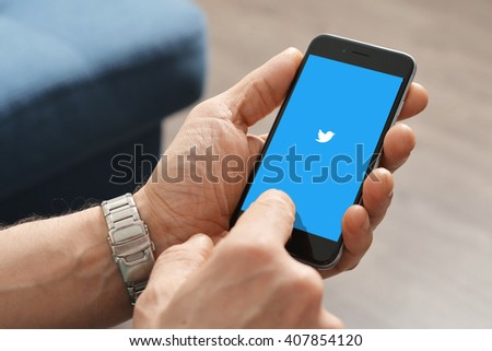 """Kiev, Ukraine - March 06, 2016: A man using Twitter app on Apple iPhone 6. Twitter is an online social networking service that enables users to send and read short messages called """"tweets"""". - stock photo"""